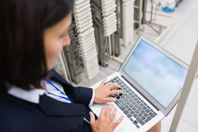 Attentive technician using laptop in server room