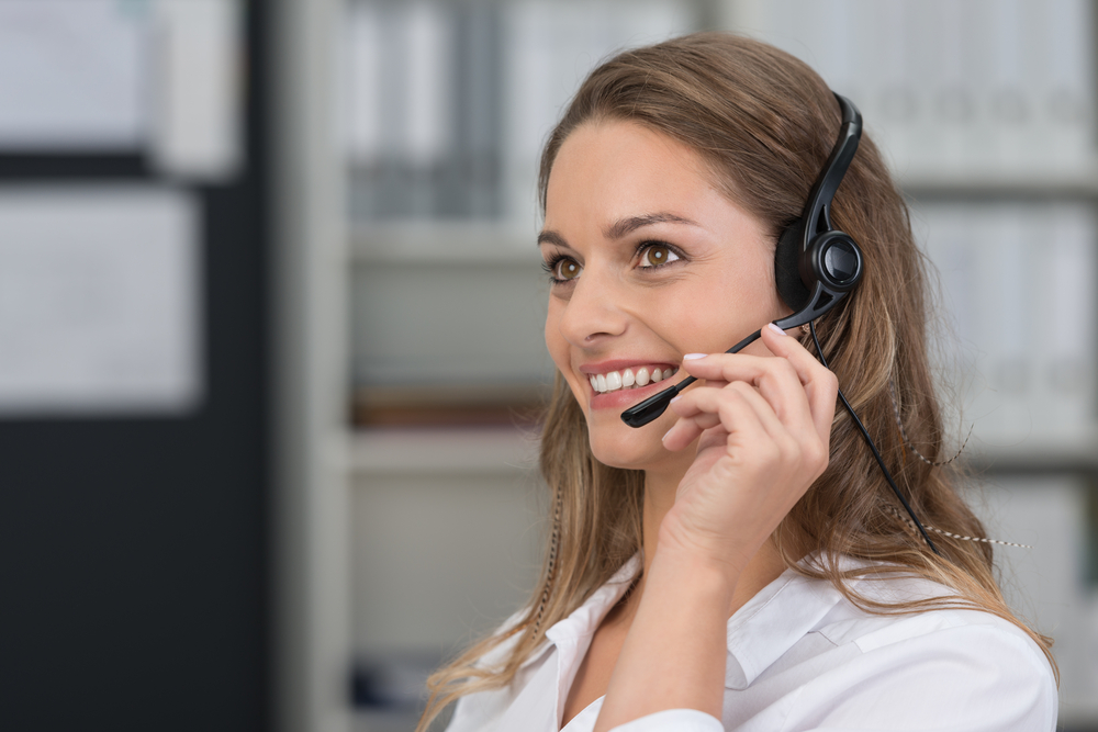 Attractive young client services assistant with a lovely smile listening to a customer on her headset as she offers assistance