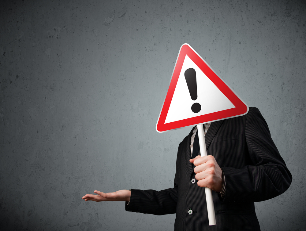 Businessman holding a red traffic triangle warning sign in front of his head-1
