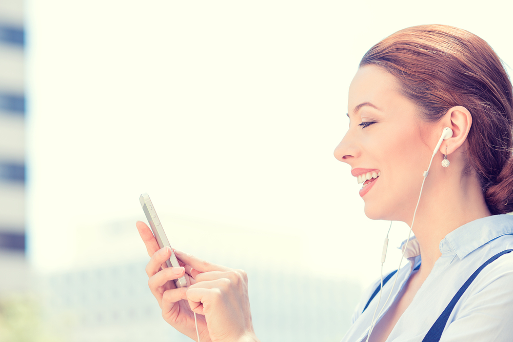 Closeup side view woman with earphones holding using smart mobile phone isolated outside corporate building background. People new generation technology concept. Customer service provider relationship