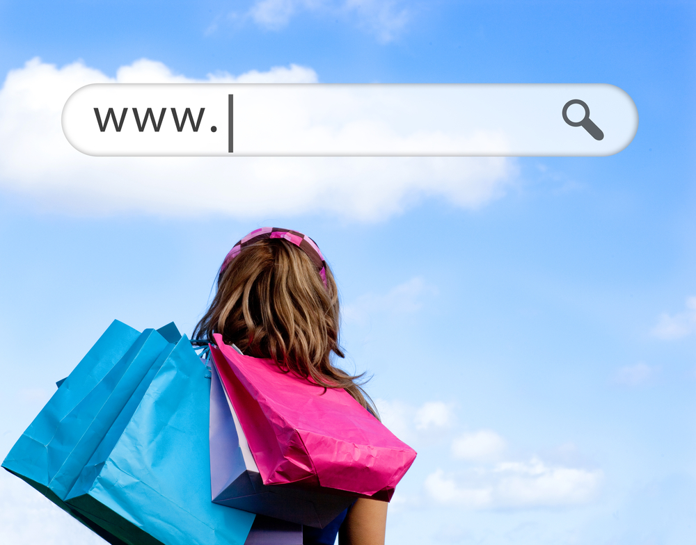 Girl holding shopping bags with address bar above against a blue sky-1